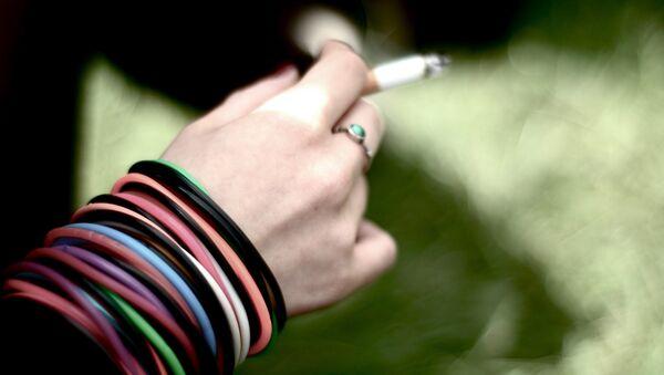 Una joven fuma un cigarrillo (Archivo) - Sputnik Mundo