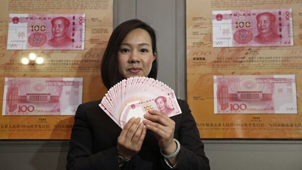 A staff member displays the new version of the 100-yuan RMB (US 15.7 dollars) banknotes for photographers at the Bank of China Tower in Hong Kong - Sputnik Mundo