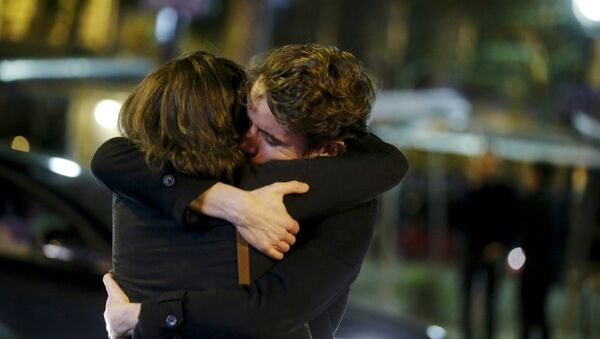 People hug on the street near the Bataclan concert hall following fatal attacks in Paris, France, November 14, 2015 - Sputnik Mundo