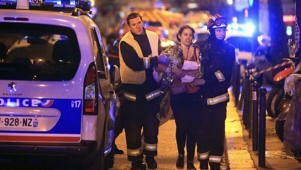 Socorristas ayudan a una mujer tras tiroteo en la sala de Bataclan en París - Sputnik Mundo