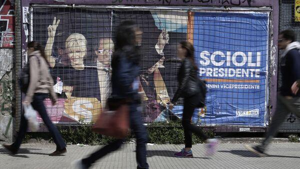 Gente paso delante de un cartel electoral en Buenos Aires - Sputnik Mundo
