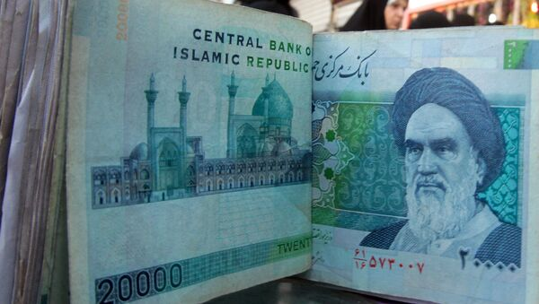 An Iraqi money dealer counts Iranian rial banknotes bearing a portrait of the late founder of the Islamic Republic of Iran, Ayatollah Ruhollah Khomeini, at an exchange office in Baghdad on February 3, 2012. - Sputnik Mundo