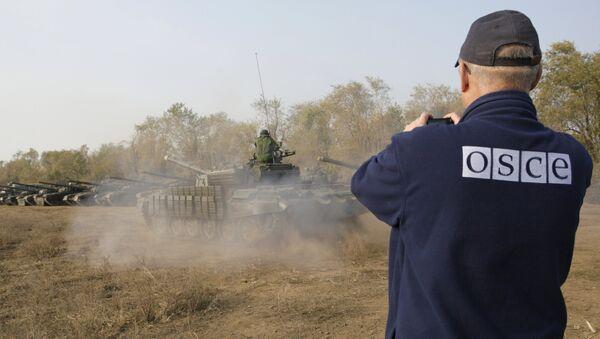 Un observador de la OSCE registra la retirada de tanques en la localidad de Stajanov, bajo control de las fuerzas de la RPL. 20 de octubre de 2015 - Sputnik Mundo