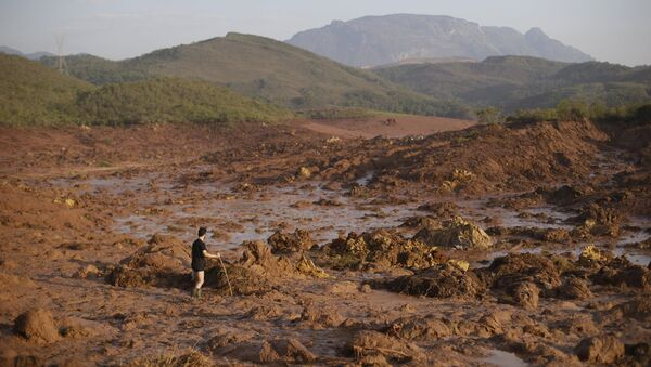 A man walks following a mudslide after a dam owned by Vale SA and BHP Billiton Ltd burst in Mariana, Brazil - Sputnik Mundo