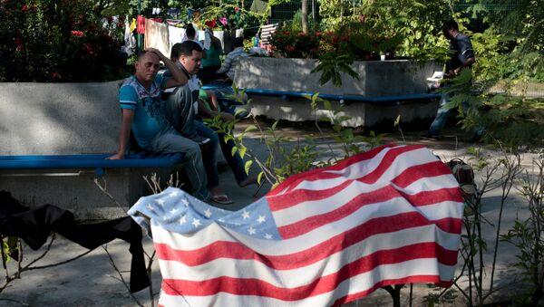Cuban migrants sit near a beach towel with the U.S. flag - Sputnik Mundo