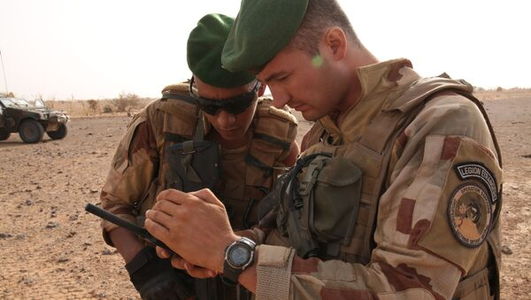French soldiers look at their sat phone as they are on patrol in the desert south of the village of Deliman, Mali - Sputnik Mundo
