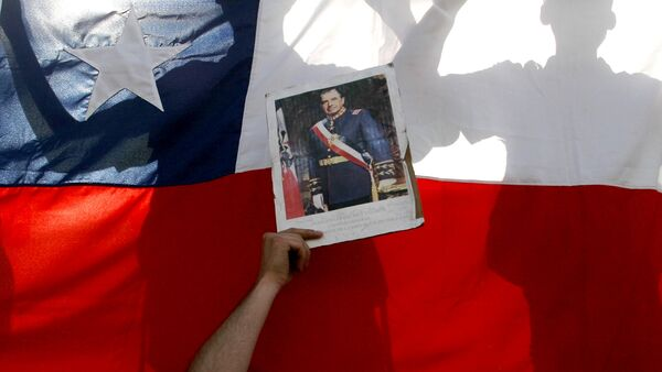 Supporters of former dictator Gen. Augusto Pinochet hold a Chilean flag and a portrait of Pinochet outside the Military Hospital in Santiago, Chile, Monday, Dec. 4, 2006 - Sputnik Mundo