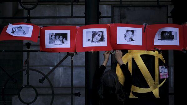 Fotos de las víctimas de femicidio en Argentina durante una manifestación en el Día Internacional contra la Violencia de Género - Sputnik Mundo