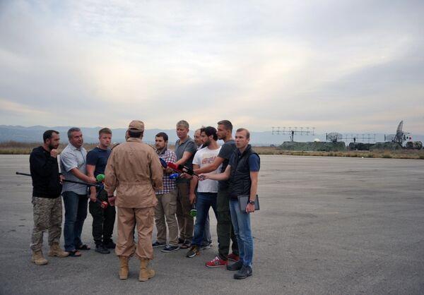 Спасенный летчик Су-24 Военно-космических сил России капитан Константин Мурахтин (в центре) отвечает на вопросы журналистов на авиабазе Хмеймим в сирийской Латакии - Sputnik Mundo