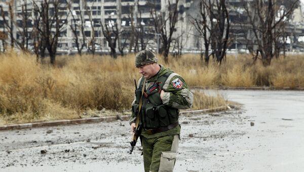 Un miliciano cerca de los edificios destruidos en Donetsk - Sputnik Mundo
