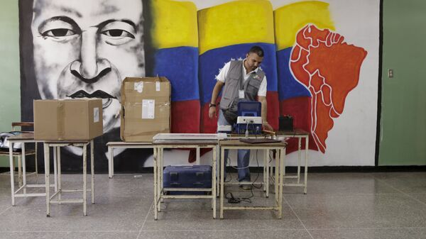 A worker of the National Electoral Council (CNE) configures a voting machine in front of a mural depicting Venezuela's late President Hugo Chavez at a school in Caracas, December 4, 2015. Venezuela will hold parliamentary elections on December 6. - Sputnik Mundo