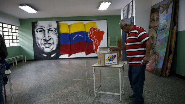 A man deposits his vote in a ballot box near a painting of Venezuela's late President Hugo Chavez during a legislative election, in Caracas - Sputnik Mundo