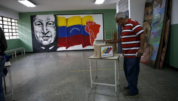 A man deposits his vote in a ballot box near a painting of Venezuela's late President Hugo Chavez during a legislative election, in Caracas - Sputnik Mundo