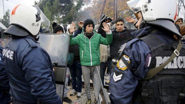 Refugiados de Marruecos enfrente del cordón de policía griega en la fronera con Macedonia - Sputnik Mundo