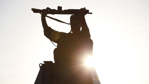 A Turkish soldier adjusts his rifle atop of an armoured vehicle as it moves to its new position at Mursitpinar near Suruc, at the Turkey-Syria border, Sunday, Oct. 5, 2014 - Sputnik Mundo