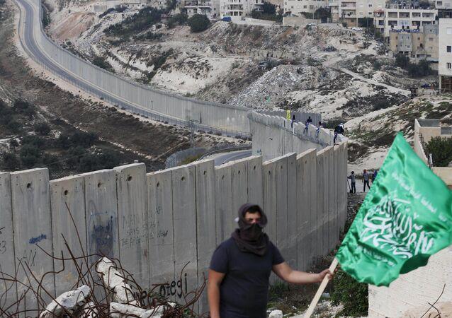 Palestino con la bandera de Hamás frente al muro israelí (archivo)