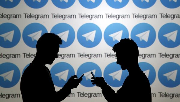 Two men pose with smartphones in front of a screen showing the Telegram logos in this picture illustration taken in Zenica, Bosnia and Herzegovina November 18, 2015. - Sputnik Mundo