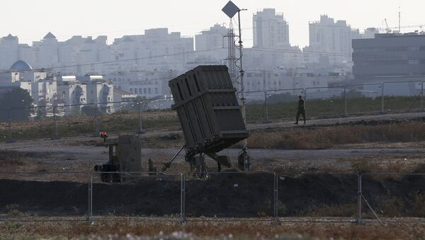 An Israeli soldier walks past an Iron Dome battery, a short-range missile defence system, designed to intercept and destroy incoming short-range rockets and artillery shells, on August 20, 2015, in the city of Ashdod. - Sputnik Mundo