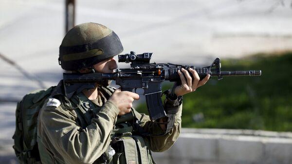 An Israeli soldier aims his weapon near the scene where a Palestinian was shot dead  - Sputnik Mundo