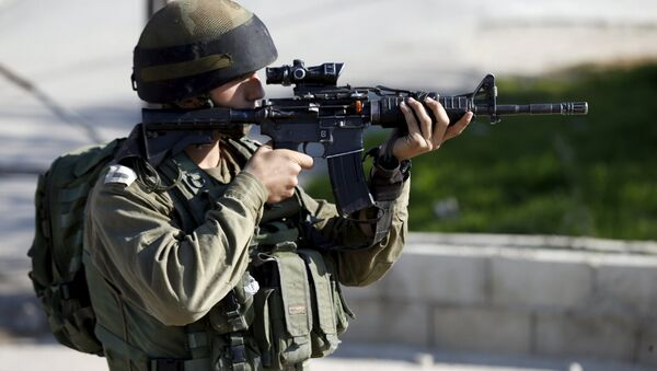 An Israeli soldier aims his weapon near the scene where a Palestinian was shot dead - Sputnik Mundo