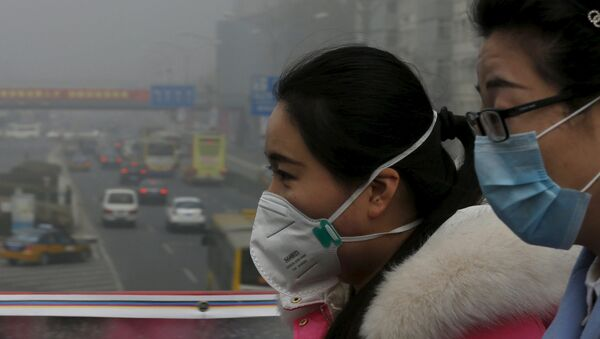 Woman wearing protective masks walk on a heavily polluted day in Beijing, December 25, 2015. - Sputnik Mundo