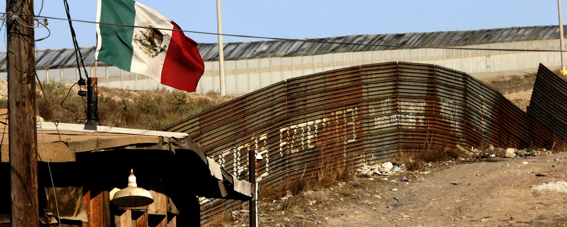 A Mexican flag waves close to the wall which separates Mexico from the United States 24 January 2006, in Tijuana, state of Baja California - Sputnik Mundo, 1920, 10.06.2021