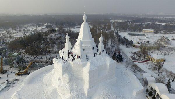 Workers polish a snow sculpture ahead of the annual Harbin International Ice and Snow Festival, in Harbin - Sputnik Mundo
