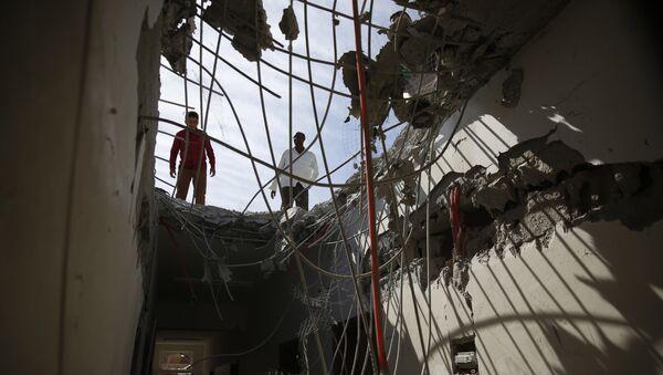 Hombres ispeccionan edificios dañados durante el bombardeo de Arabia Saudí en Sanaa - Sputnik Mundo