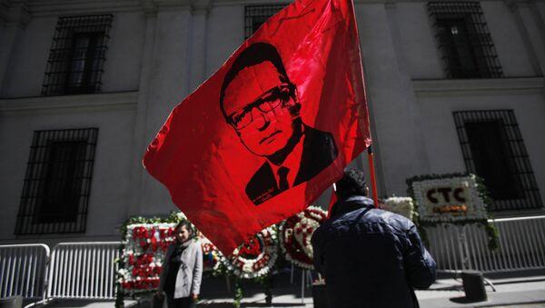 Un hombre alza la bandera con la cara de Salvador Allende frente al Palacio de La Moneda en Chile - Sputnik Mundo