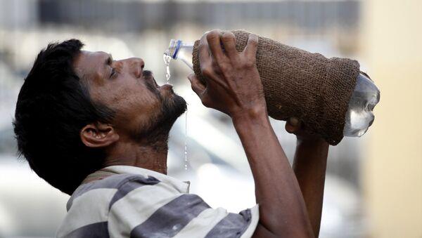 Un hombre indio bebe agua - Sputnik Mundo