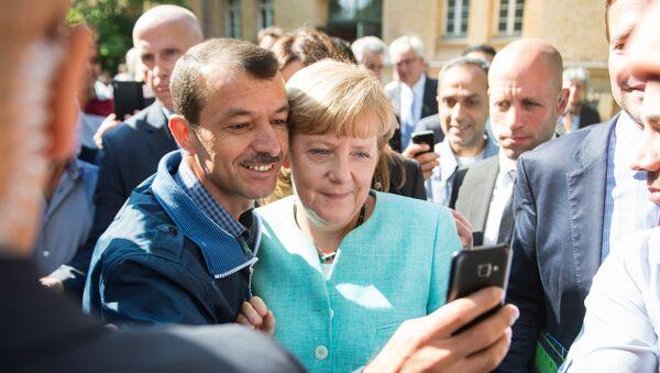 Un refugiado se hace un selfie con Angela Merkel (archivo) - Sputnik Mundo