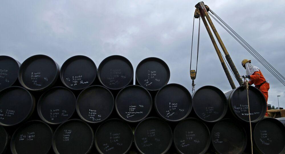Un obrero se prerpara a transportar petróleo