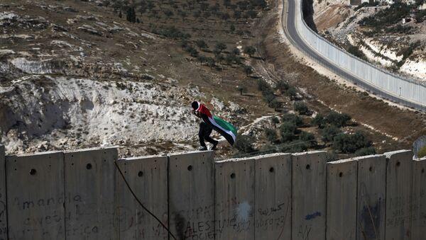 Un palestino camina sobre el muro de Cisjordania, construido por Israel - Sputnik Mundo