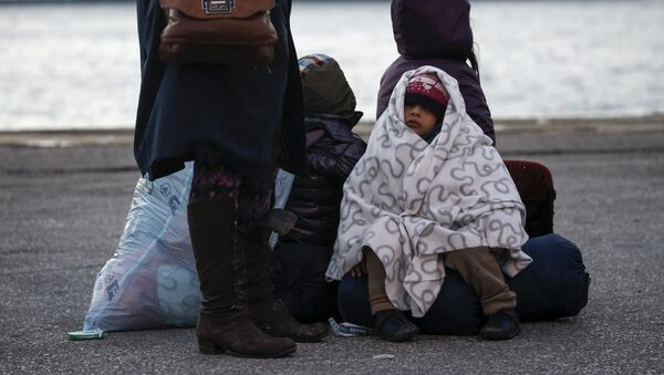 A migrant girl is covered with a blanket as refugees and migrants arrive aboard the passenger ferry Nissos Rodos at the port of Piraeus, near Athens, Greece, January 13, 2016. - Sputnik Mundo