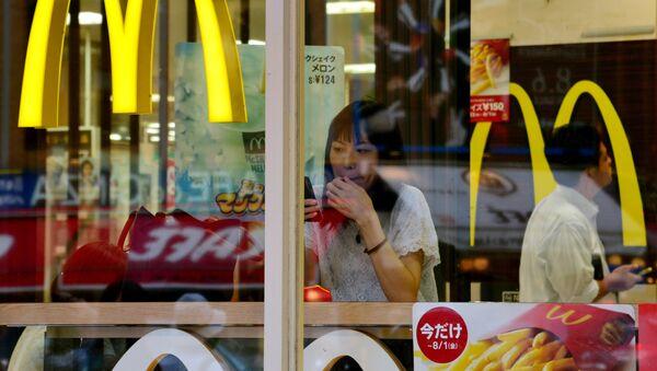 A woman uses her smartphone inside a McDonald's restaurant in Tokyo on July 23, 2014. - Sputnik Mundo