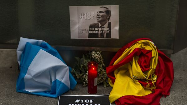 The Argentinean and Spanish flag, a candle, flowers and banners reading telling the truth should not cost one's life are placed in front of the Argentinean Embassy as people gather for justice and against impunity in the case of the mysterious death of late prosecutor Alberto Nisman, in Madrid, Spain, Wednesday, Feb. 18, 2015. - Sputnik Mundo