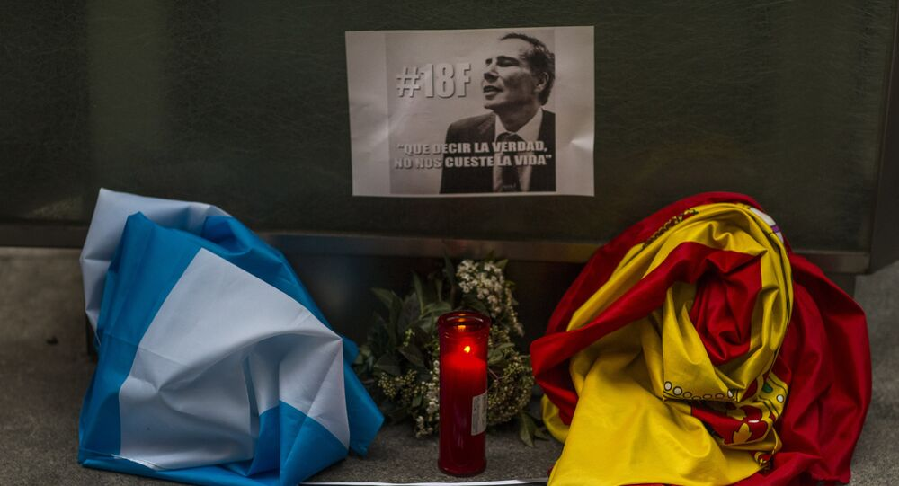 The Argentinean and Spanish flag, a candle, flowers and banners reading telling the truth should not cost one's life are placed in front of the Argentinean Embassy as people gather for justice and against impunity in the case of the mysterious death of late prosecutor Alberto Nisman, in Madrid, Spain, Wednesday, Feb. 18, 2015.