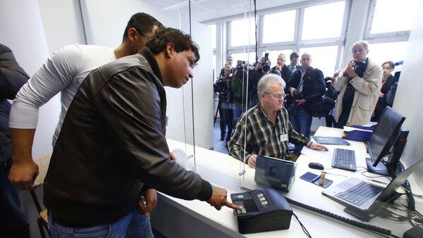 La toma de una huella dactilar en un centro de refugiados en Alemania - Sputnik Mundo