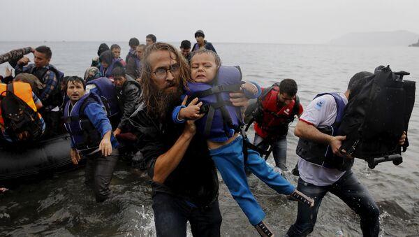 Un voluntario lleva a una pequeña refugiada siria tras un naufragio cerca de las costas de Turquía - Sputnik Mundo