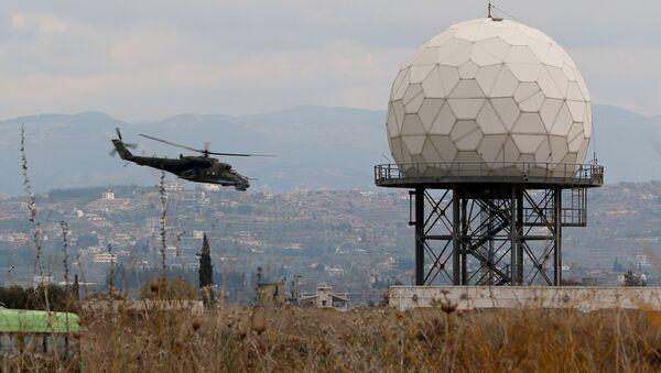 Un helicóptero vuela cerca de un radar en la base militar rusa Hmeymim en Siria - Sputnik Mundo