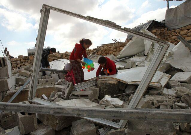 Niños palestinos buscan juguetes en los restos de su casa