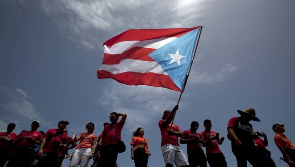 A man waves a national flag of Puerto Rico (archive) - Sputnik Mundo
