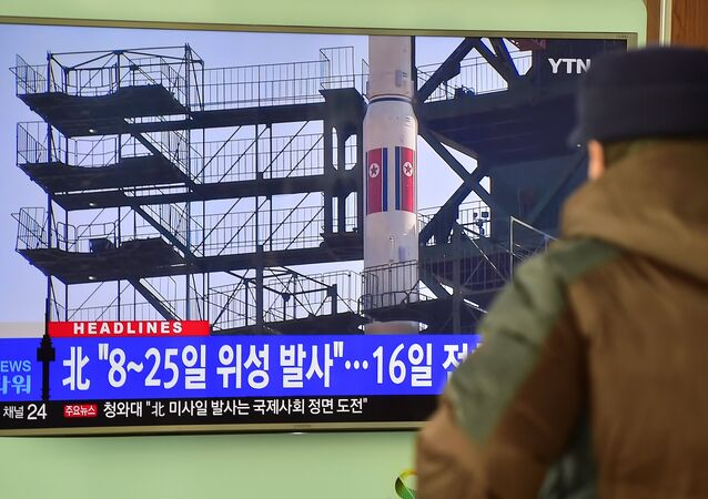 Un hombre mira un informe por la tele sobre el lanzamiento de cohete planeado mientras que en la pantalla aparece el video sobre el cohete-portador Unha-3 (lanzado en 2012). El 3 de febrero del 2016