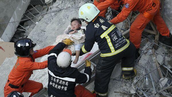 Equipo de rescate ayuda a un niño tras el sismo en Taiwán - Sputnik Mundo