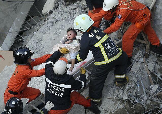 Equipo de rescate ayuda a un niño tras el sismo en Taiwán