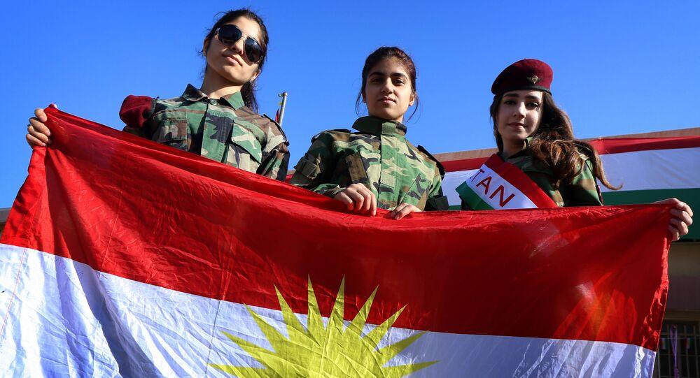 Iraqi Kurdish girls carry a Kurdistan flag during the celebration of Flag Day in the northern city of Arbil, the capital of the autonomous Kurdish region in northern Iraq