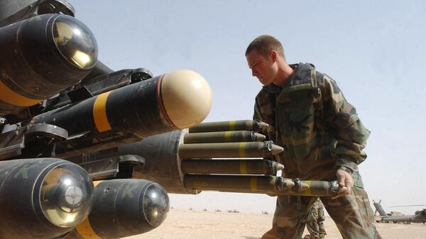 US Army armament crew specialist Michael Mayo, from Florida, loads the rocket pod of an an Apache AH-64D attack helicopter also armed with Hellfire missiles at left - Sputnik Mundo