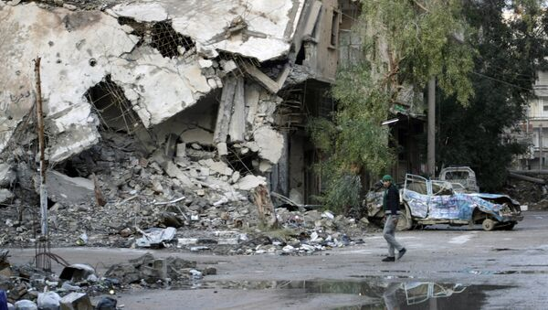 A man walks in a devastated street of the eastern Syrian town of Deir Ezzor on February 15, 2014. - Sputnik Mundo