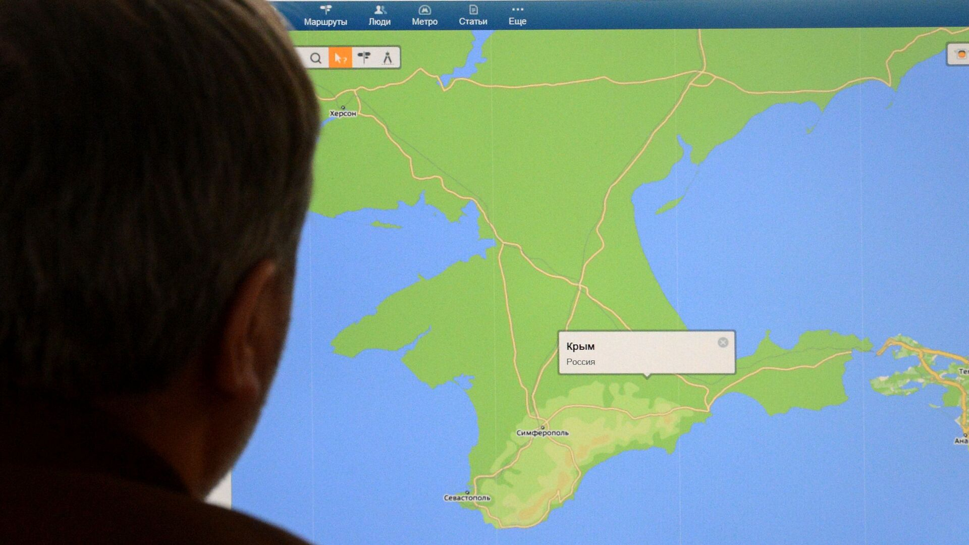 A man looks in Moscow on March 21, 2014, at a computer screen displaying a map of Crimean peninsula - Sputnik Mundo, 1920, 24.07.2021