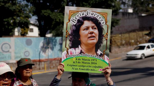 An activist holds up a photo of slain environmental rights activist Berta Caceres during a protest to mark International Women's Day outside the presidential house in Tegucigalpa - Sputnik Mundo